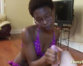 Naked man sits on armchair and nerdy black girl gives him handjob