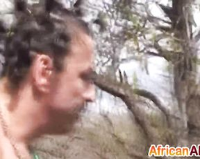Impudent man dominates over naked Ebony slave somewhere in savanna