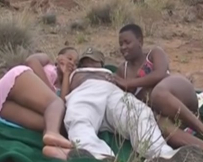 Man puts blanket on the ground and naked black girls serve his cock
