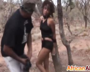 Two guys spank and dominate naked black slut who is tied up to tree