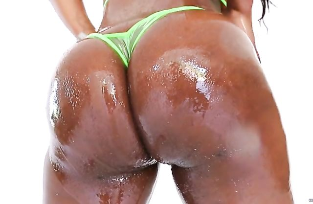 Oiled-up ebony hottie with a big round butt reveals her big stretched pussy