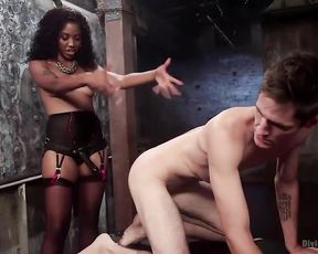 Ebony mistress with strapon dominates over naked guy and his friend