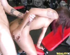Tattooed guy and naked Ebony athlete have a lot of fun in empty gym