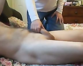 Naked guy lies on the bed and girl gives him handjob in amateur video