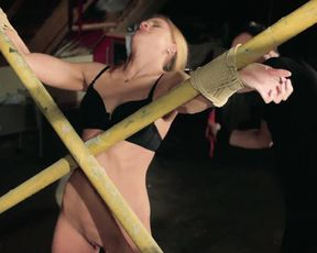 Man ties blonde girl to X-cross and treats naked vagina with vibrator