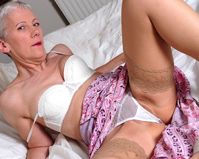 Naked mature woman with short haircut sticks pussy with grand vibrator