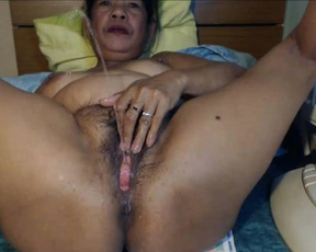 Naked girl over fifty shoves fingers and dildo in hairy pussy on webcam