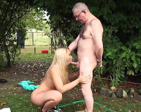 Old man meets with young blonde girl to have naked encounter in garden