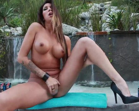 Busty MILF fingers naked vagina with vibro-ring on by fountain