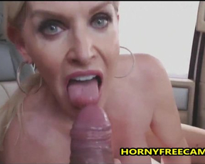 Dirty-minded MILF with big earrings sucks cameraguy's naked cock in car