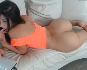 Dark-haired girl with naked ass lies on the couch and looks so sexy
