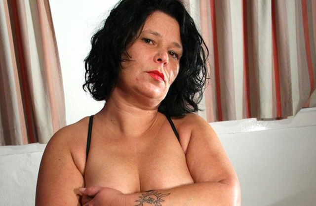 Raven-haired woman with red lips enjoys naked masturbation on the bed