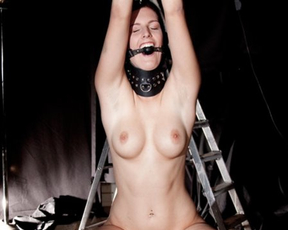 Gagged naked brunette with a collar tried to scream being tied up