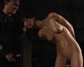 Man in black dominates over naked brunette slave with slim waist