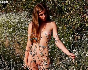 Super luscious naked girl with a gorgeous body spreads thighs on the grass showing amazing twat