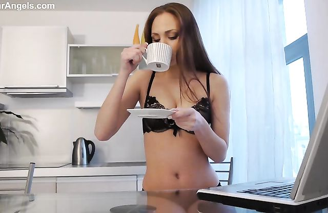 Hot naked girl starts her day with a cup of coffee and poses nicely on a couch