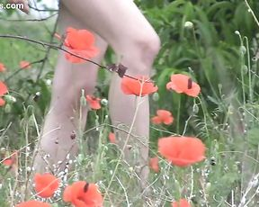 Blonde naked girl walking around in the field and stretching her holes for the camera