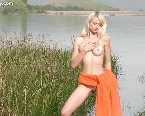 Topnotch naked girl with fair hair demonstrates her amazing lean body on the lake
