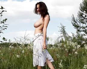 Naked girl with big amazing boobs enjoys herself in the field playing a solo on cam
