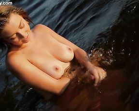 Tanned naked girl poses in the water showing off her magnificent firm boobs