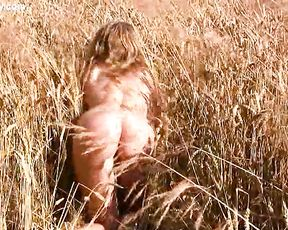 Naked girl with fair hair demonstrates her outstanding body in the field on rye