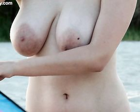 Smiling naked girl with massive boobs playing with a kite on the seashore