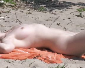 Naked girl with white skin goes naughty on the beach plays a solo on the sand