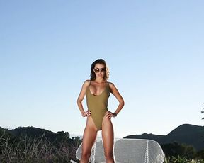 Mouthwatering naked girl demonstrates her ideal body and long legs outdoors