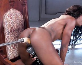 Naked ebony slut girl with a muscular body enjoys drilling by a sex machine