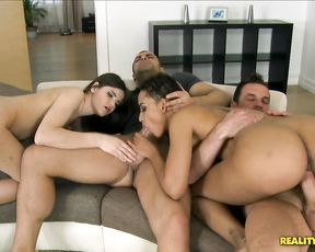Two naked bitches get their pussies rammed hard by two studs on the couch