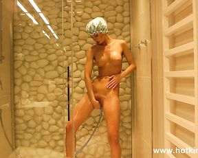 Naked girl plays with the shower cap in her shaved pussy during a raw solo