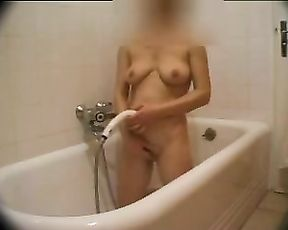 Slender girl gets naked to take a shower and masturbates pussy with water