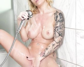 Very sexy chick with a tattooed body enjoys having a shower and masturbating